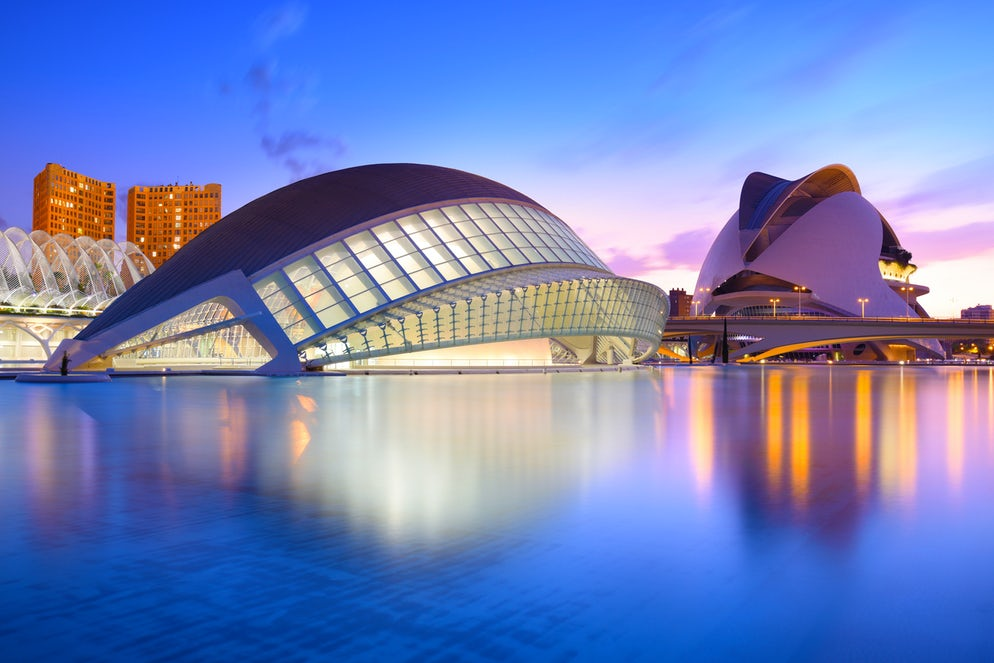 Picture Credits to cittadinodelmondo.The city of the Arts and Sciences and his reflection in the water at dusk. This complex of modern buildings was designed by the architect Santiago Calatrava.